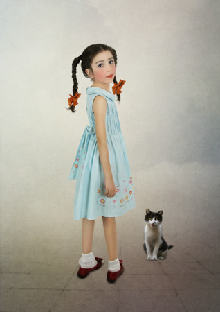 Little girl with pigtails looking over her shoulder and kitten sitting on the floor Stock Photo