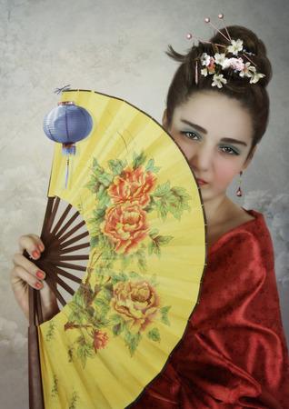 barrettes: La ragazza in kimono rosso con ventola in mano Archivio Fotografico