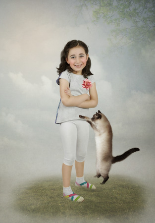 The little girl with a smile on his face, his arms crossed and the cat photo