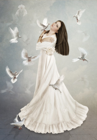 idyll: The young girl with long hair in white dress, surrounded by doves Stock Photo