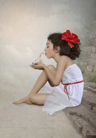 The little girl with red bow kiss dove photo
