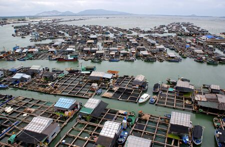 Birds-eye view on a floating fishing village with boats, houses and wharves photo