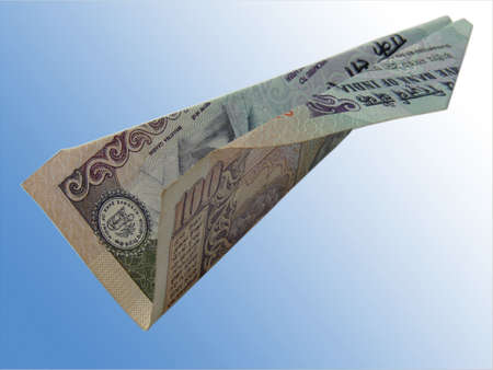 A image showing an airplane isolated with made up of Indian 100 Rs. Note flying in air. This can be conceptual image for online Indian money transfer or like that.