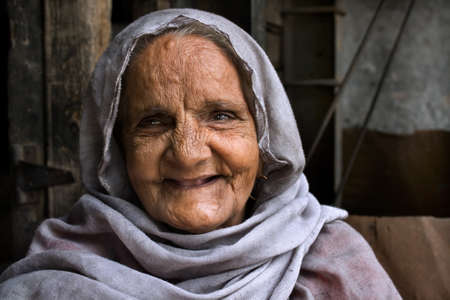 An Indian smiling old lady expressing positively in simple outfit.