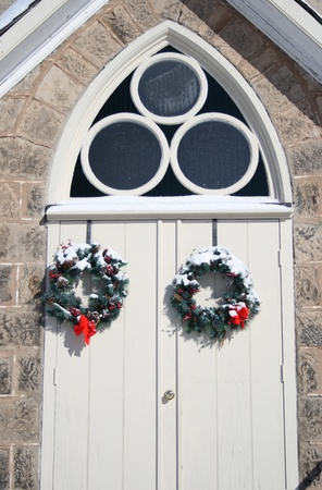chr: arched church doors during winter with christmas wreaths