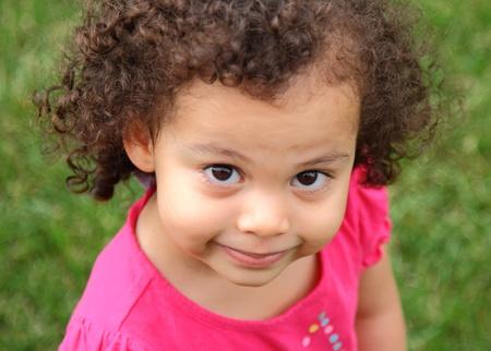 Hermosa chica posando con poca birracial sonrisa Foto de archivo - 13242035