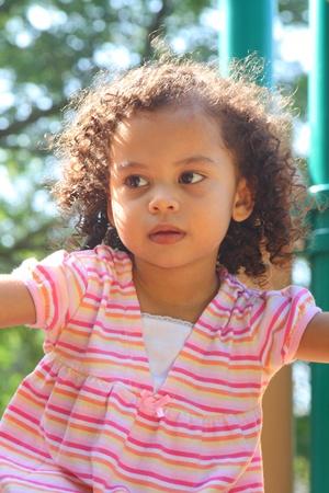 beautiful biracial little girl playing  photo