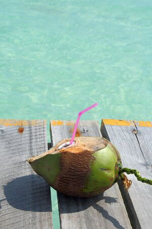 coconut drink overlooking tropical beach photo