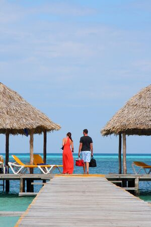 couple in romantic walk along tropical ocean pier photo