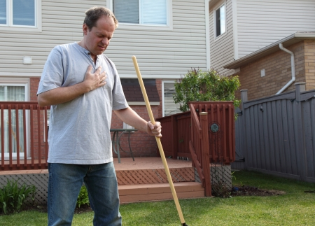 man having a heart attack chest pains while doing yard work
