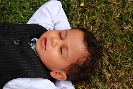 young boy lying and relaxing on the grass peaceful photo