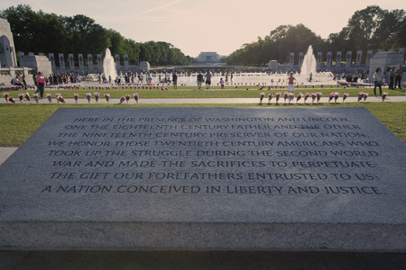 plaque: WASHINGTON D.C. - MAY 25 2014: Dedicatory plaque and WWII memorial with Lincoln Memorial in background.