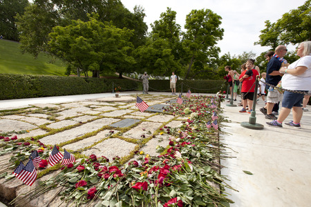 WASHINGTON D.C., MAY 26, 2014: Tourists leave flowers for fallen soldiers at Arlington National Cemetery during Memorial Day weekend on May 26, 2014.