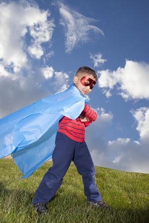 little boy superhero against blue sky photo