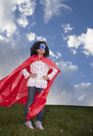 little girl superhero against blue sky Standard-Bild