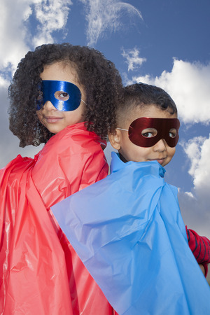 little boy and girl superheros against blue sky photo