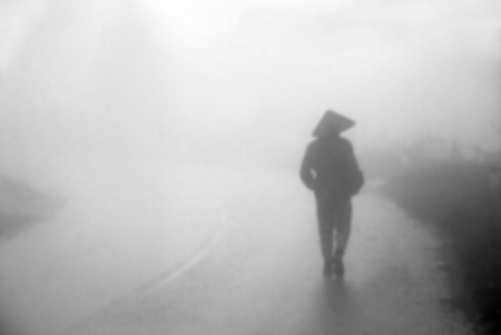 alone person: blur picture ,man walk into the misty foggy road,dark atmosphere Stock Photo