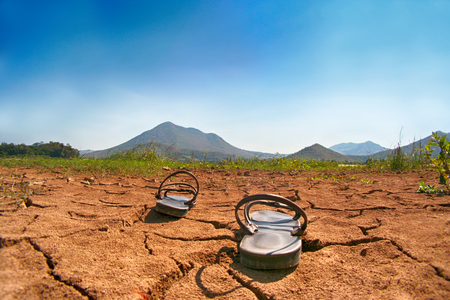 Shoes, put on dry land,drought land and cracked earth landscape