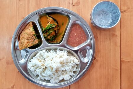 Rice with Curry in Rice dish tray and delicious food on wood background