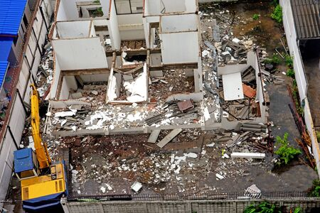 Top view of damage area, crash and collapse building with excavator to manage area,under construction area with truck