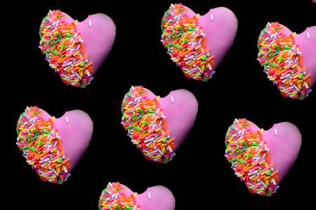 Heart shape of donut covered by pink chocolate rainbow sprinkle decoration on isolate,Valentine day Stock Photo