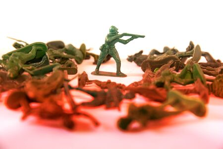 small green soldier model action shooting gun with other soldier model onthe floor, colorful image