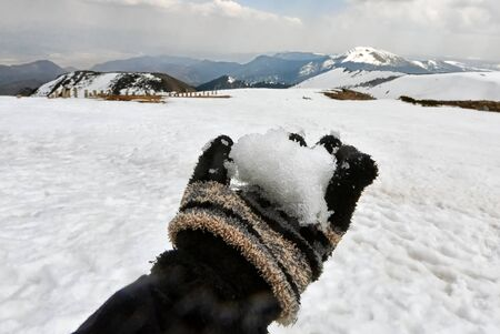 Cold snow in hand behind snow mountain Stock Photo