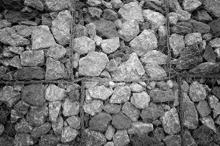 Le filet fait de fil de fer recouvrant le mur plein de rochers