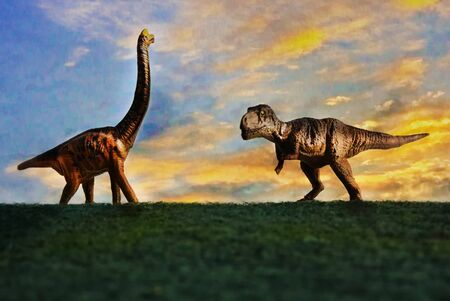 Tyrannosaurus rex or t-rex infront colorful sky and foliage in background Stock Photo
