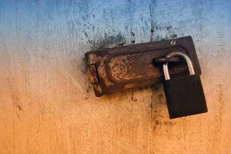 Old wooden doors locked by rusty padlock,iron latch,key lock