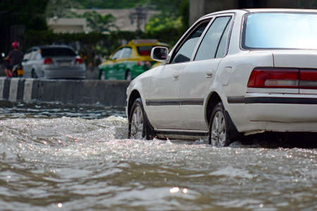 more floods and flooded cars ,car driving flood water on a road