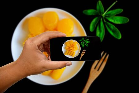 Take a photo with a mobile phone with ancient Thai Dessert, thai sweet dessert in bowl on black background,egg yoke fudge balls cooked in syrup, Pinched gold egg yolks, appetizer