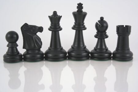 an image of black chess pieces and reflection