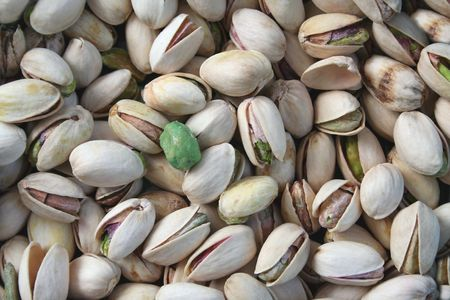 an image of Pistachios with a single wasabi pea photo