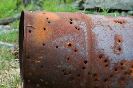 an image of a Rusty 50 gallon Drum with bullet holes