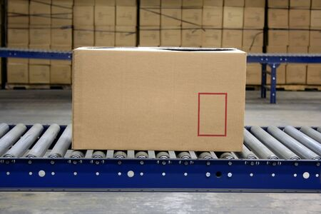 Carton on conveyor rollers in a warehouse Stock Photo