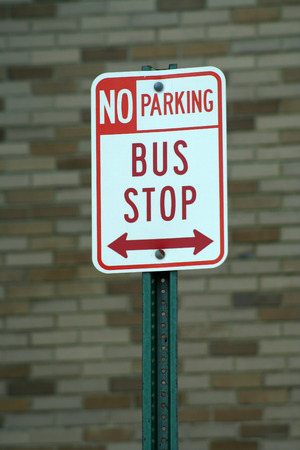 Bus stop and no parking sign against a brick wall Stock Photo - 1416472