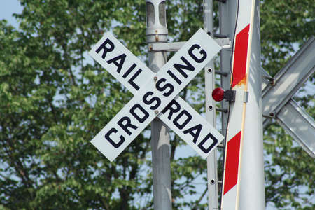 Railroad crossing sign  with light with trees photo