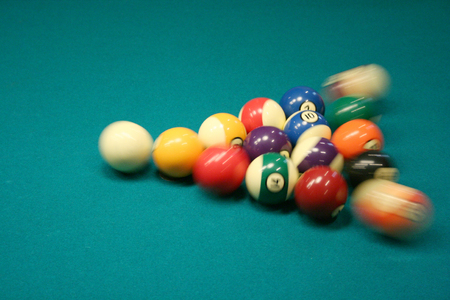 8 ball being broken on green pool table photo