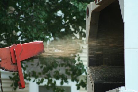 Wood chipper spraying chips into a truck Stock Photo