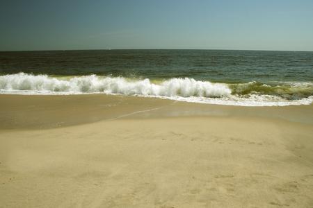 beachcomb: Ocean Wave crashing on a sandy beach Stock Photo