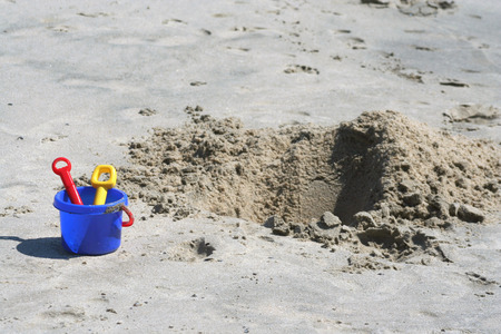 sand pit: A Shovel, pail and sand pit on the beach