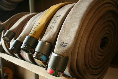 Fire Hoses lined up inside a firehouse Stock Photo