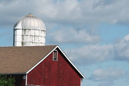 Red barn and silo against a cloudy sky