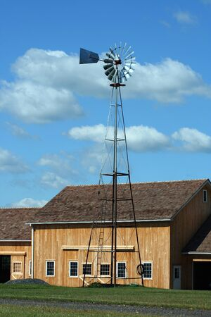 A Windmill with new barn against a cloudy blue sky Stock Photo - 1693023