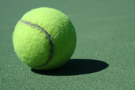 A Tennis ball on a green court Stock Photo