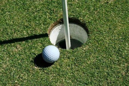 旗のポールと穴の近くの緑の上のゴルフボール