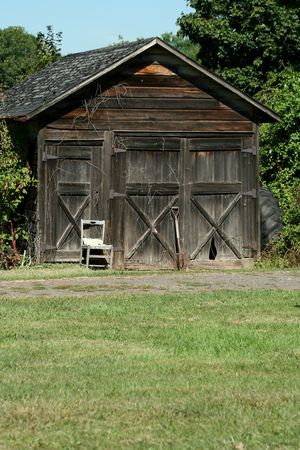 An Old wooden barn with grass and sky