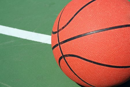 A Basketball on green court with white line photo