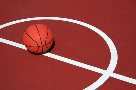 A Basketball at center court on a red court Imagens